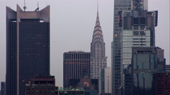 The Chrysler Building in the midtown Manhattan skyline lighting up Stock Footage