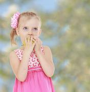 little girl in a pink dress bites an Apple, pale green backgroun - stock photo