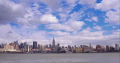 Timelapse of clouds in a blue sky passing over the midtown Manhattan skyline - stock footage