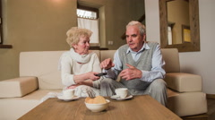 Grandmother give TV remote to elderly husband 4K Stock Footage
