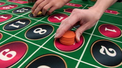 Casino: Sliding Shot Of Gamblers Putting Chips On Numbers On Roulette Table Stock Footage