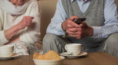 Elderly person holding a TV remote controller 4K Stock Footage