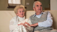 Lovely senior couple on sofa looking of camera Stock Footage
