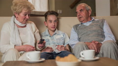 Young grandson watching television with grandparents on sofa 4K Stock Footage