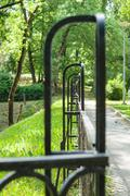 Abstract vanishing decorative wrought iron fence in summer park Stock Photos