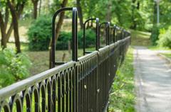Vanishing decorative wrought iron fence in sunny park Stock Photos