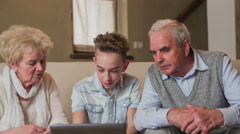 Grandson showing something on laptop to grandparents 4K Stock Footage