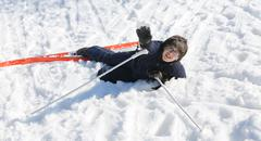 young boy asks for help after the fall from snow skiing - stock photo