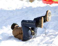Child enjoying sledding on snow in the mountains in winter Stock Photos
