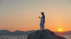 A woman in a white dress standing on a large rock in the water on a background Stock Footage