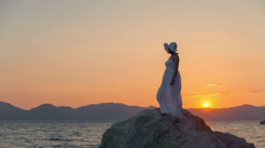 Happy woman on windy beach at sunset background in white dress shows like. RAW Stock Footage