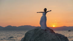 Woman on the background of sunset with their hands up happy. RAW video record Stock Footage