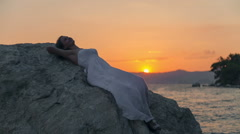 Young lady relaxing in tropical beach at sunset. RAW video record Stock Footage