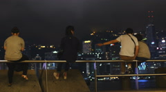 Friends relax looking out at Victoria harbor HK 4K Stock Footage