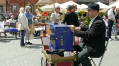 Man plays on barrel organ at the Market Place in the old town. Warsaw, Poland Stock Footage