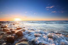 Sunset over the Baltic sea. The pebbly beach in Rozewie - stock photo