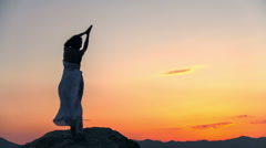 Silhouette of a girl standing on stones in the sea at sunset background. RAW Stock Footage