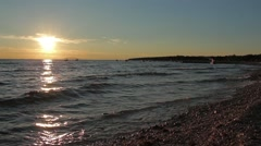Beautiful sea sunset with rocky beach and gentle waves Stock Footage