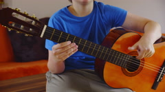 Young person play guitar strings in living room 4K Stock Footage