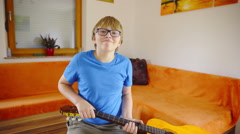 Boy swinging around acoustic guitar at home 4K Stock Footage