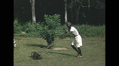 Vintage 16mm film, 1952, Malaysia, man mowing lawn Stock Footage