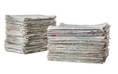 Two piles of newspapers on a white background - stock photo