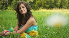 Woman in colorful dress sitting on grass Stock Footage