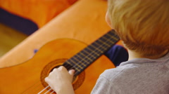 Child play on guitar and adjusting strings 4K Stock Footage