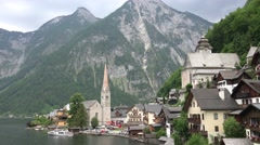 4k Alps valley village center Hallstatt with church and lake Stock Footage