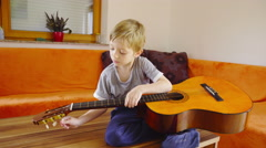 Kid trying to play guitar 4K Stock Footage