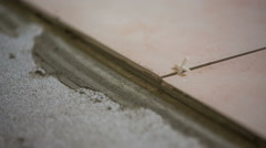 Tiles on concrete floor glued together close up Stock Footage