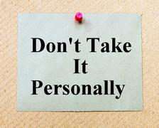 Don't Take It Personally written on paper note pinned with red thumbtack - stock photo