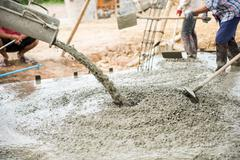 Concrete pouring during commercial concreting floors of buildings in construc Stock Photos