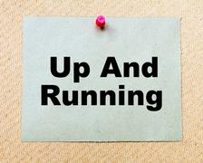 Up And Running  written on paper note pinned with red thumbtack  Stock Photos