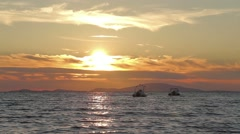 Spectacular perfect sea sunset with motorboats, island on horizon, long shot Stock Footage
