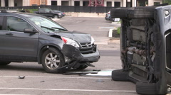 Car accident with car rolled over on it's side at city intersection - stock footage