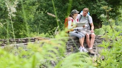 Couple of hikers reading map on stone bridge Stock Footage