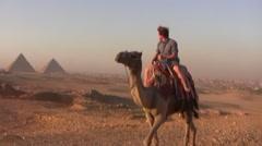 Man Riding a Camel Near the Pyramids of Giza Stock Footage