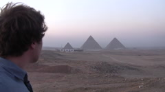 Young Man Looks on to the Pyramids of Giza Stock Footage