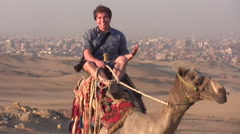 Young Man Riding a Camel Near the Pyramids of Giza - stock footage