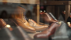 Men's shoes in a shop window display. - stock footage