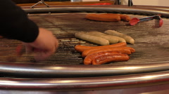Cook grilling sausages on a big grill - stock footage