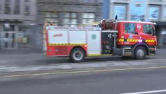 Fire engine  on way to emergency though city street Stock Footage