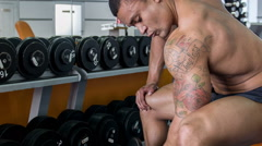 Handsome heavy-weight athlete is training with dumbbell Stock Footage