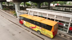 Yellow-orange Transjakarta bus departs from stop, next bus pass by without stop Stock Footage