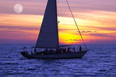 Sailboat sunset silhouette with people and full moon rising in the sky. - stock photo