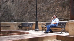 OLD MAN TALKING ON CELLPHONE on bench in small park - Old San Juan. Puerto Rico Stock Footage