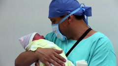 MEDIUM SHOT. New father meets and holds his newborn daughter in the labor room. Stock Footage