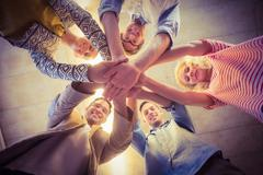 Happy business team joining their hands - stock photo