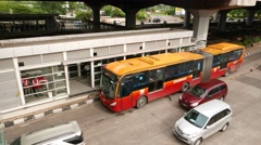 Double bus departs from stop, turn left crossing whole roadway, tracking shot Stock Footage